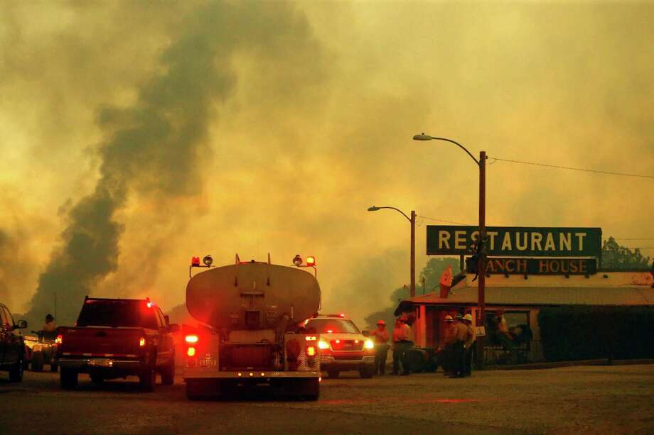 Firefighters monitor a restaurant as the Yarnell Hill Fire burns on Sunday, June 30, 2013 near Yarnell, Ariz. The fire started Friday and picked up momentum as the area experienced high temperatures, low humidity and windy conditions. It has forced the evacuation of residents in the Peeples Valley area and in the town of Yarnell. (AP Photo/The Arizona Republic, David Kadlubowski) Photo: David Kadlubowski, Associated Press / The Arizona Republic