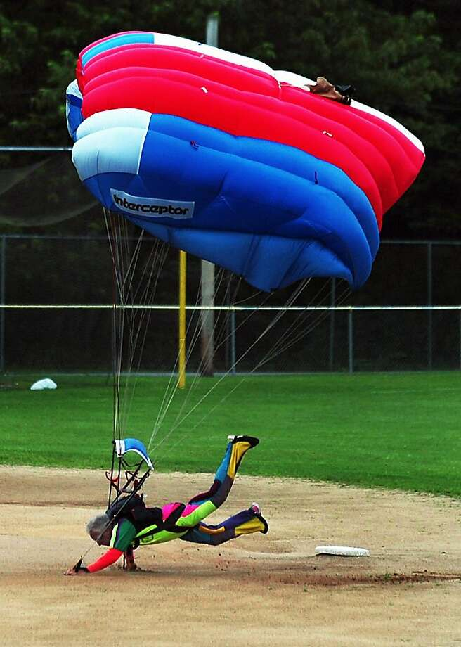 Safe at second! Skydiver Tom Casper lands with an appropriate flop during the Throop Cow Flop Carnival in 
