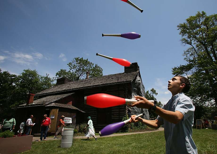 Justin Finkel, 18 from Detroit juggles outside of the Palmer Log Cabin that was open for tours during Log Cabin Day at Palmer Park, Sunday, June 30, 2013. The cabin was built by Senator Thomas Palmer for his wife Lizzie Palmer in 1885 and in 1894, the Senator donated the first 120 acres that would become Palmer Park. (AP Photo/Detroit Free Press , Diane Weiss) DETROIT NEWS OUT,  MAGS OUT, NO SALES, MANDATORY CREDIT DETROIT FREE PRESS Photo: Diane Weiss, Associated Press
