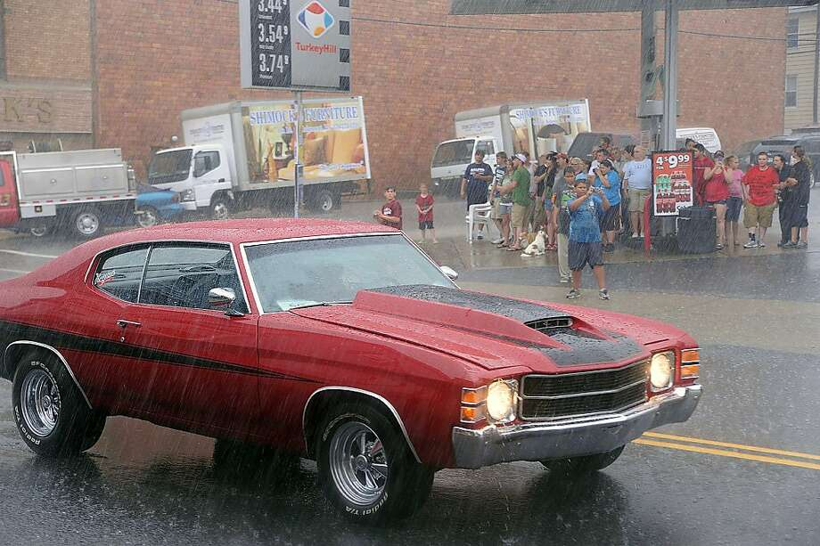 A classic Chevrolet Chevelle makes its way down through rain as spectators seek shelter during the 11th Great Kulpmont Cruise on Sunday, June 30, 2013, in Kulpmont, Pa. Approximately 190 classic cars and trucks turned out for the event. (AP Photo/The News-Item, Mike Staugaitis) Photo: Mike Staugaitis, Associated Press