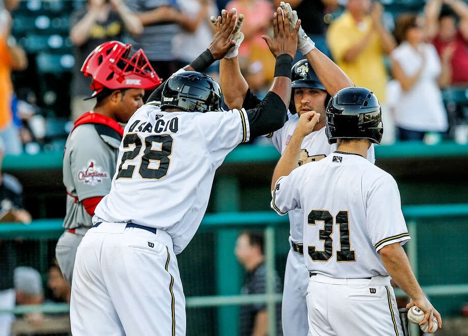Jake Blackwood (second from right) of the Missions exchanges high-fives with Yeison Asencio at home plate after hitting a two-run homer in the sixth inning. Blackwood's blast gave his club a 3-1 lead. Photo: Marvin Pfeiffer / San Antonio Express-News