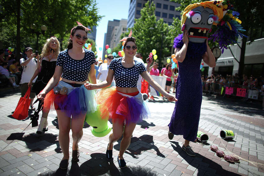 Sara Koelsch, left, and Jenny Glatt march with PopCap Games during the annual Pride Parade on Sunday, June 30, 2013 in Seattle. Hundreds of thousands of people came to downtown Seattle to celebrate Pride, on the heels of a U.S. Supreme Court decision on DOMA and California's Proposition 8 and last year's legalization of same-sex marriage by voters in Washington State.