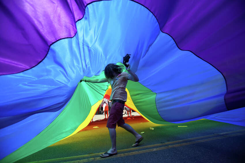 A man runs under the pride flag during the annual Pride Parade on Sunday, June 30, 2013 in Seattle. Hundreds of thousands of people came to downtown Seattle to celebrate Pride.