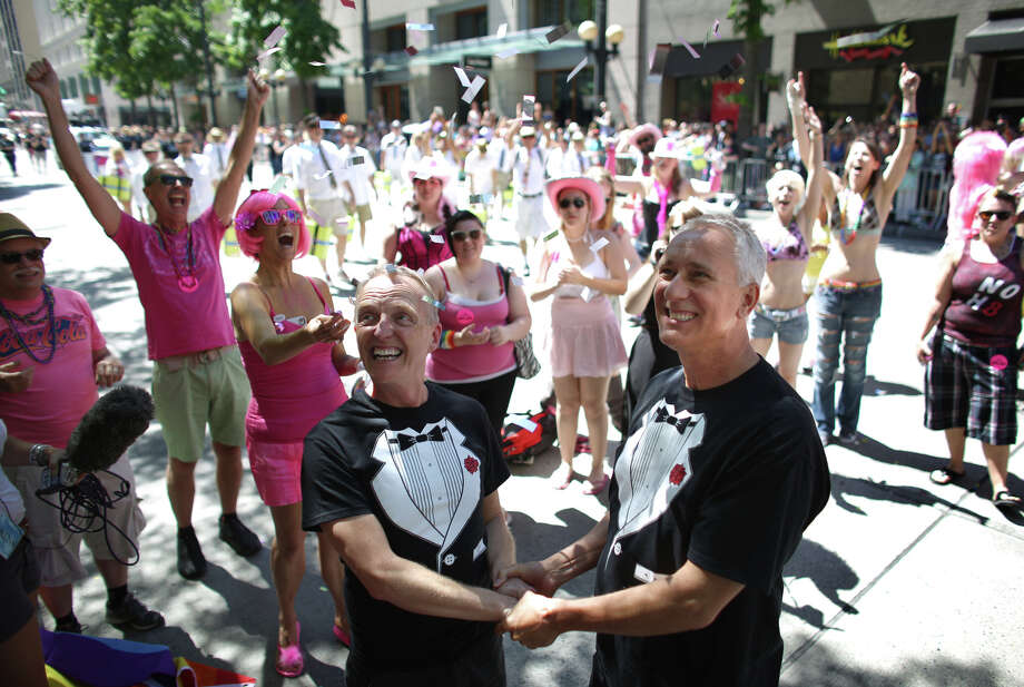 "Jim Webber, left, and his partner Mark Stanley are married in a ""flash wedding"" during the annual Pride Parade on Sunday, June 30, 2013 in Seattle. During the parade they were married in front of the Westlake Park announcer's stage. Photo: JOSHUA TRUJILLO, SEATTLEPI.COM"