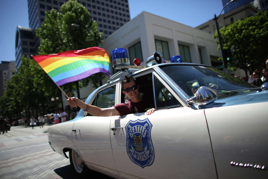 A pride flag is waved from a classic Seattle Police cruiser during the annual Pride Parade. Photo: JOSHUA TRUJILLO, SEATTLEPI.COM