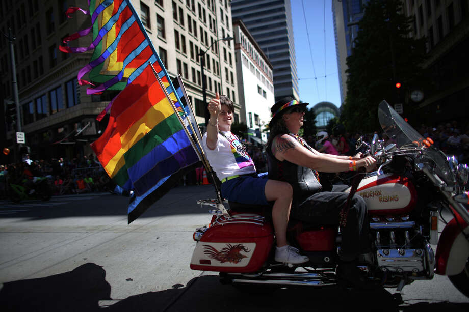 Seattle City Councilmember Sally Clark rides on the back of a motorcycle during the annual Pride Parade. Photo: JOSHUA TRUJILLO, SEATTLEPI.COM