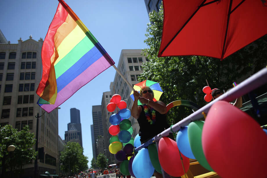 A woman waves a pride flag during the annual Pride Parade. Photo: JOSHUA TRUJILLO, SEATTLEPI.COM