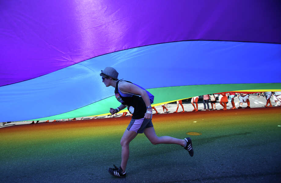 A woman runs under a giant pride flag. Photo: JOSHUA TRUJILLO, SEATTLEPI.COM