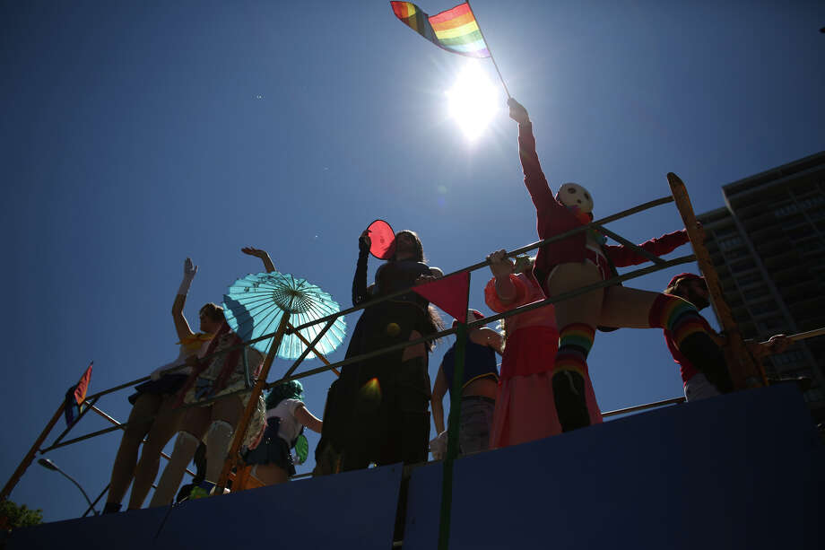 Participants wave flags from a float. Photo: JOSHUA TRUJILLO, SEATTLEPI.COM