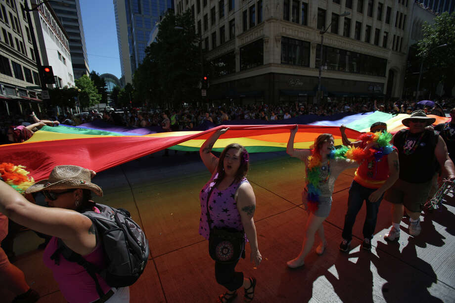 Participants hoist the pride flag during the annual Pride Parade. Photo: JOSHUA TRUJILLO, SEATTLEPI.COM