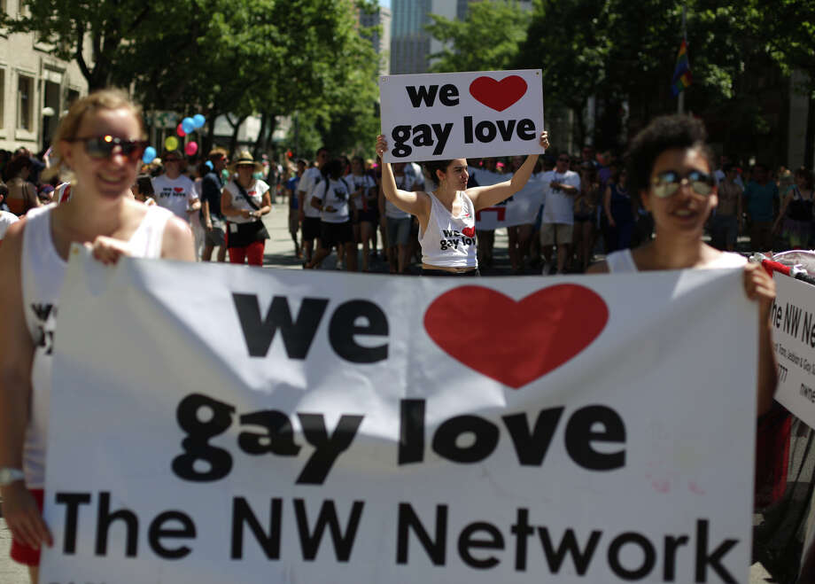 Participants hoist signs during the annual Pride Parade. Photo: JOSHUA TRUJILLO, SEATTLEPI.COM