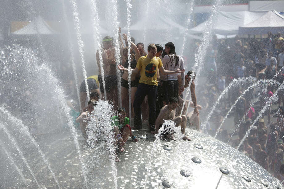 People climb onto the International Fountain at the Seattle Center during the annual Pride Parade. Photo: JOSHUA TRUJILLO, SEATTLEPI.COM