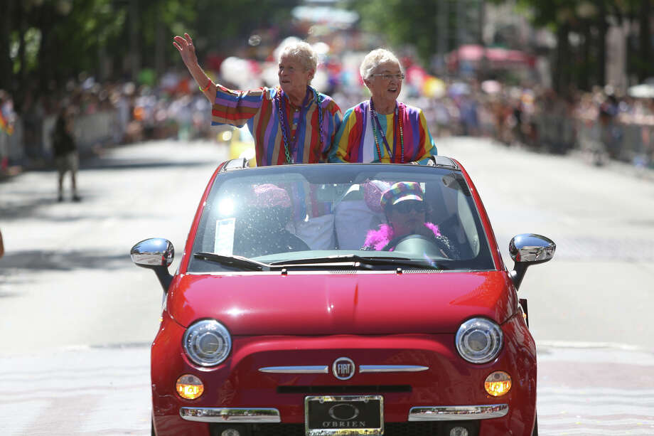 Jane Lighty and Pete-e Peterson ride as the grand marshalls during the annual Pride Parade on Sunday, June 30, 2013 in Seattle. They were among he first to be issue a marriage license after the passage of referendum 74. Hundreds of thousands of people came to downtown Seattle to celebrate Pride, on the heels of a U.S. Supreme Court decision on DOMA and California's Proposition 8 and last year's legalization of same-sex marriage by voters in Washington State. Photo: JOSHUA TRUJILLO, SEATTLEPI.COM