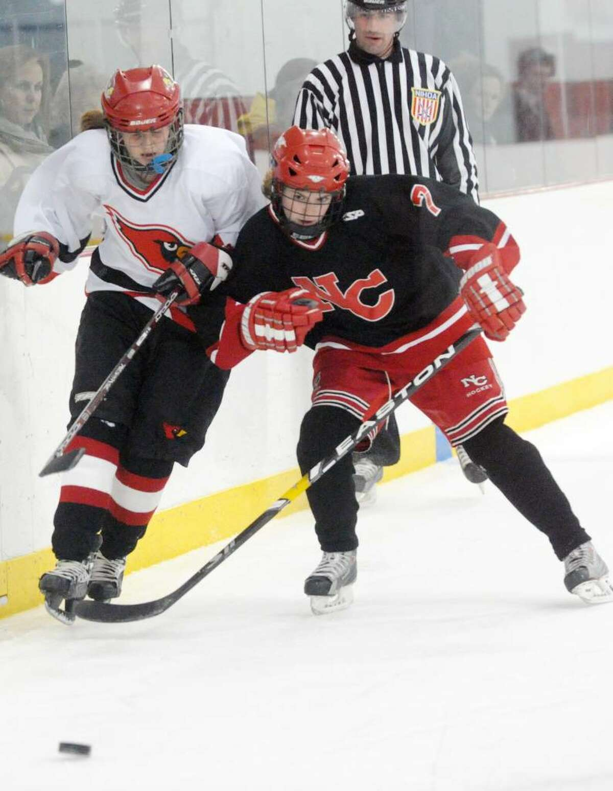 New Canaan's Abbey Buckenheimer shoulders Greenwich's Olivia Tapsall as Greenwich High hosts New Canaan in a girls hockey game at Dorothy Hamill Saturday afternoon, January 16, 2010.