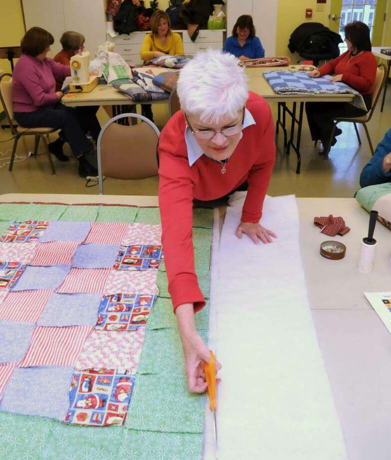 Lynn Wyckoff, of New Fairfield, CT, cuts batting for a quilt that the Helping Hands Quilters, a part of the Community Service Club, are making. The club, working out of the New Fairfield Senior Center, in New Fairfield, CT on Thursday, Dec. 17, 2009, will soon complete their 1000th quilt. Photo: Jay Weir / The News-Times