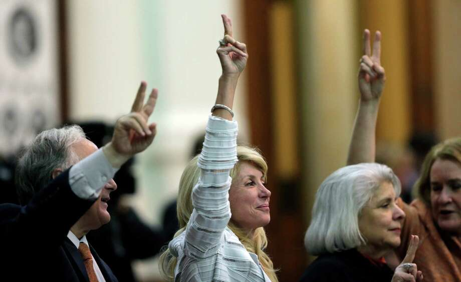 "FILE -  In this Tuesday, June 25, 2013, file photo, Sen. Wendy Davis, D-Fort Worth, center, holds up two fingers to signal a ""No"" vote as the session where tshe tried to filibuster an abortion bill draws to a close, in Austin, Texas. Hundreds of abortion rights activists ensured that the first special legislative session descended into chaos. Now, Texas Gov. Rick Perry has convened a second one and urged abortion opponents to respond with mobilizations of their own. Photo: Eric Gay"