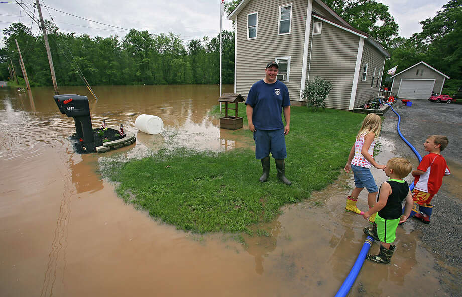 Jason Van der Hoff, and his children, Caitlin, Jacob, and Drew, stand in front of their home by the Onieda River, in Oneida, N.Y., Friday, June 28, 2013.  Flooded streets were also reported in the city of Oneida in nearby Madison County, while residents in Johnsburg in the eastern Adirondacks were being asked to stay off the roads until flooding subsided.  (AP Photo/The Syracuse Newspapers, Dick Blume) NO SALES ORG XMIT: NYSYR103 Photo: Dick Blume, AP / The Syracuse Newspapers