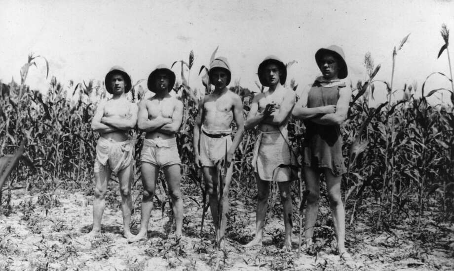 Circa 1912:  Five European  men in sarong shorts and pith helmets standing in a maize field somewhere in China.  (Photo by Hulton Archive/Getty Images)
