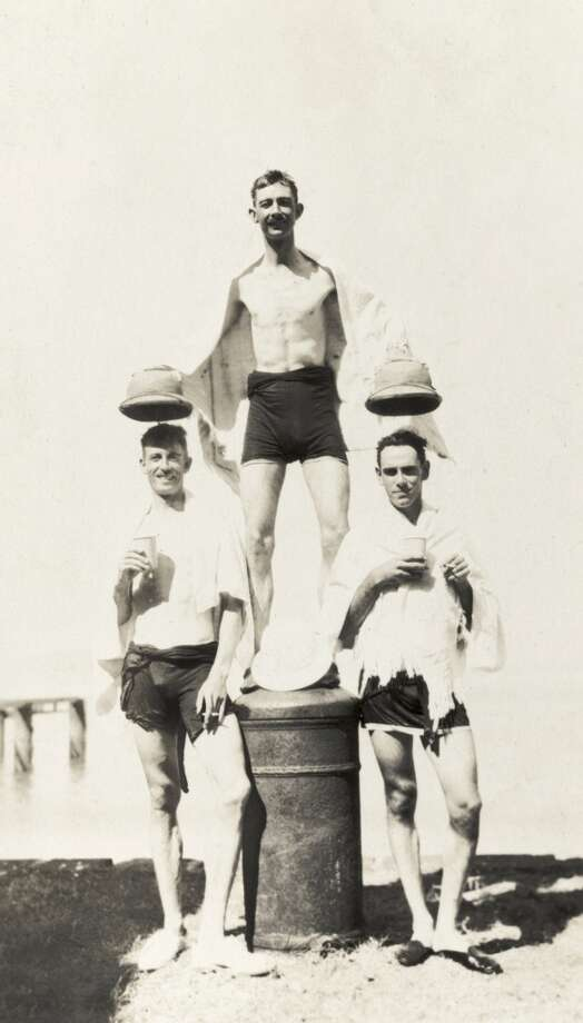 Three European men pose for a comical photograph after a swim, wearing only swimming trunks with towels wrapped around their shoulders. A man identified as Brigadier Winthrop stands on a mooring post between his companions, holding their solatopi hats several inches above their heads. India, 1920.  (Photo by Images of Empire/Universal Images Group via Getty Images)