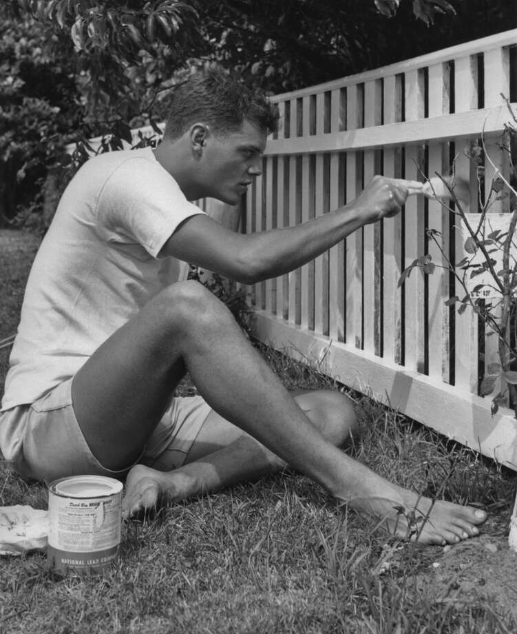 A man sits whitewashing a garden fence circa 1940. (Photo by J. L. Hamar/Archive Photos/Getty Images)