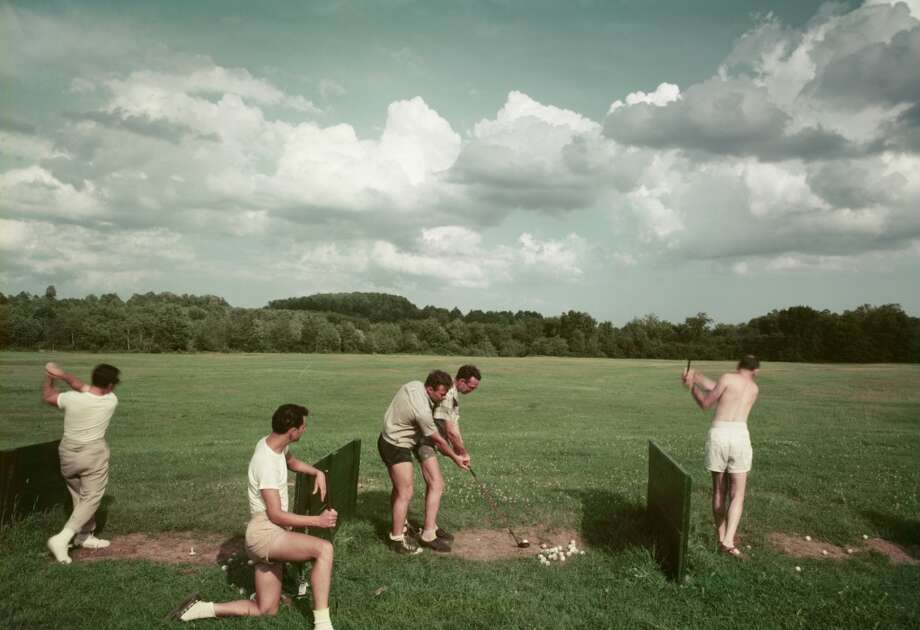A group of men golf on a driving range on the grounds of the Riverside Hotel, Divine Corners, New York, 1950s or 1960s. In the center, one golfer's swing is adjusted by an instructor. (Photo by Aladdin Color Inc/Getty Images)