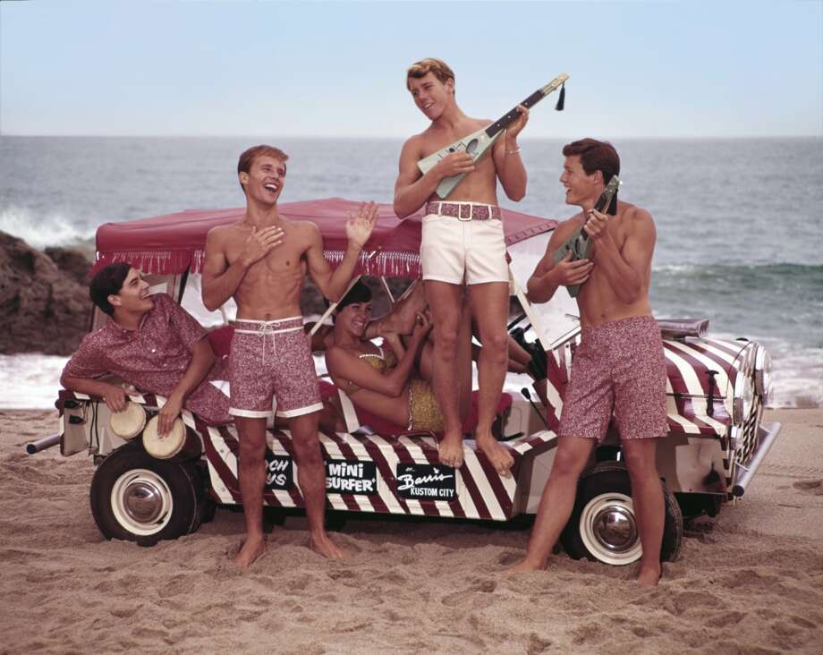 Four guys and a girl, all students, sit or stand next to a Barris surf car, while wearing the latest fashion in Jantzen bathing suits, California, 1966. (Photo by Tom Kelley/Getty Images)