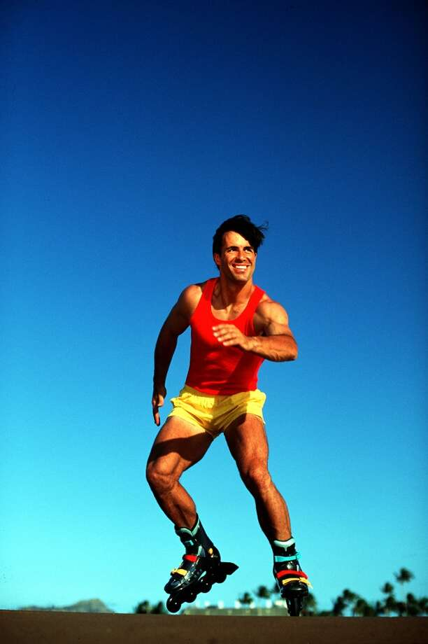 A model wearing a red vest and yellow shorts rollerblading.  (Photo by Paul Popper/Popperfoto/Getty Images)