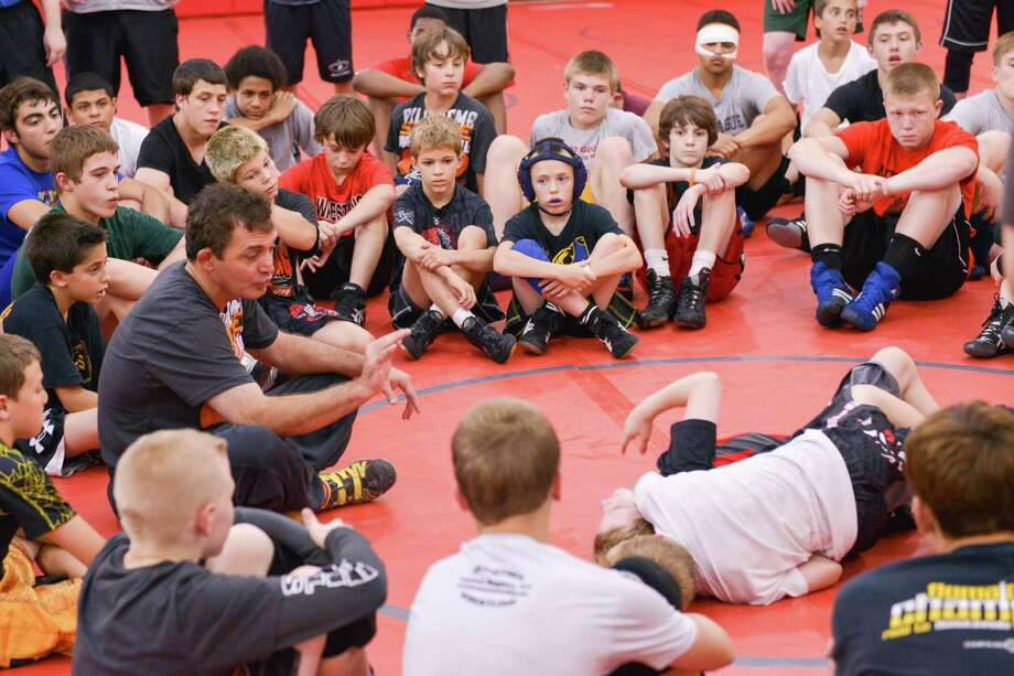 Oklahoma State University wrestling coach and Olympic gold medalist John Smith teaches wrestling moves while participants look on at a wrestling camp session held Sunday, June 30, 2013, at Niskayuna High School. (Shawn Morgan / Special to the Times Union)