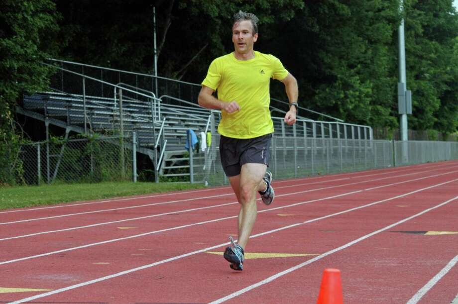 Darien's Justin Lubeley, 36, crosses the finish line for the Westport Road Runners Summer Series 2.3-miler in a winning time of 12:37 on Saturday morning at Staples High. Photo: Contributed Photo