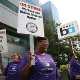 OAKLAND, CA - JULY 01:  Amalgamated Transit Union workers hold signs as they strike outside of a Bay Area Rapid Transit (BART) station on July 1, 2013 in Oakland, California. Hundreds of thousands of San Francisco Bay Area commuters are scrambling to find ways to work after the Bay Area Rapid Transit (BART) workers from the Amalgamated Transit Union Local 1555 went on strike at midnight after contract negotiations with management fell apart on Sunday. Train operators, mechanics, station agents and maintenance workers are seeking a five percent wage increase and are fighting management who want to have workers to begin contributing to their pensions, pay more for health insurance and reduce overtime expenses.  (Photo by Justin Sullivan/Getty Images)