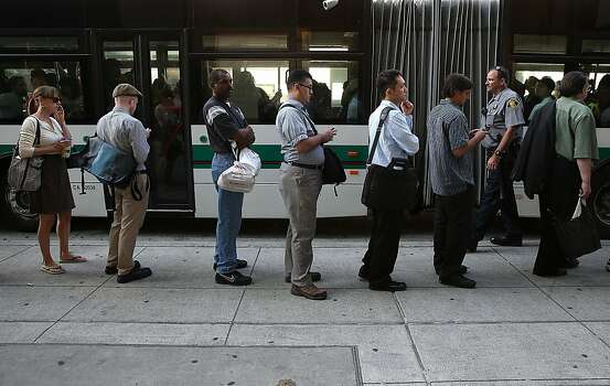 OAKLAND, CA - JULY 01:  Commuters line up to wait for an AC Transit bus on July 1, 2013 in Oakland, California. Hundreds of thousands of San Francisco Bay Area commuters are scrambling to find ways to work after the Bay Area Rapid Transit (BART) workers from the Amalgamated Transit Union Local 1555 went on strike at midnight after contract negotiations with management fell apart on Sunday. Train operators, mechanics, station agents and maintenance workers are seeking a five percent wage increase and are fighting management who want to have workers to begin contributing to their pensions, pay more for health insurance and reduce overtime expenses.  (Photo by Justin Sullivan/Getty Images) Photo: Justin Sullivan, Getty Images