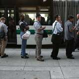 OAKLAND, CA - JULY 01:  Commuters line up to wait for an AC Transit bus on July 1, 2013 in Oakland, California. Hundreds of thousands of San Francisco Bay Area commuters are scrambling to find ways to work after the Bay Area Rapid Transit (BART) workers from the Amalgamated Transit Union Local 1555 went on strike at midnight after contract negotiations with management fell apart on Sunday. Train operators, mechanics, station agents and maintenance workers are seeking a five percent wage increase and are fighting management who want to have workers to begin contributing to their pensions, pay more for health insurance and reduce overtime expenses.  (Photo by Justin Sullivan/Getty Images)