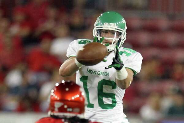 Derrick Thompson of the University of North Texas keeps his eyes on a pass as Trevon Stewart closes in during the second quarter of a NCAA football game Saturday, Oct. 6, 2012, in Houston.