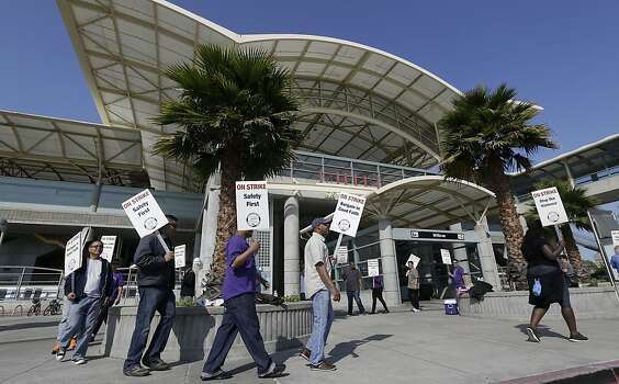 Bay Area Rapid Transit workers picket outside of a station in Millbrae, Calif., Monday, July 1, 2013. Early Monday, July 1, 2013, two of San Francisco Bay Area Rapid Transit's largest unions went on strike after weekend talks with management failed to produce a new contract. (AP Photo/Jeff Chiu) Photo: Jeff Chiu, Associated Press