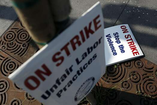 Picket signs sit against a tree facing the street during strikes against BART outside of the West Oakland BART station in Oakland, Calif. on July 1, 2013. Photo: Ian C. Bates, The Chronicle