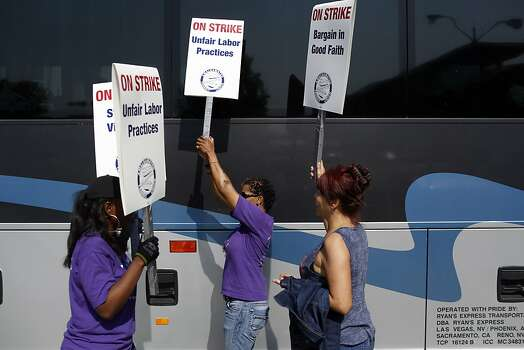 Picketers walk back in forth along full buses commissioned by BART to bring normal BART riders to San Francisco during strikes against BART outside of the West Oakland BART station in Oakland, Calif. on July 1, 2013. Photo: Ian C. Bates, The Chronicle