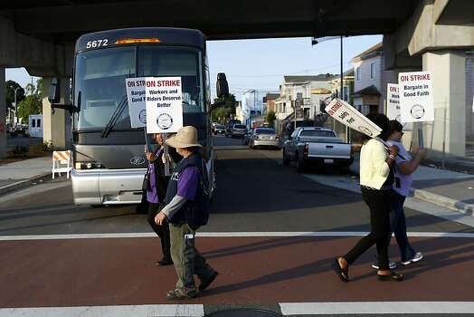 Strikers block a bus employed by BART carrying passengers to San Francisco outside of the West Oakland BART station during strikes against BART in Oakland, Calif. on July 1, 2013. Photo: Ian C. Bates, The Chronicle
