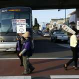 Strikers block a bus employed by BART carrying passengers to San Francisco outside of the West Oakland BART station during strikes against BART in Oakland, Calif. on July 1, 2013.