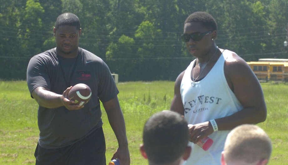 "Atlanta Falcons defensive tackle Corey Peters, left, and Jasper center Terrell Cuney, right, interact with campers at the ""Spoonful of Hope"" football camp hosted by Jasper native and Atlanta Falcons linebacker Sean Weahterspoon Photo: David Berry"