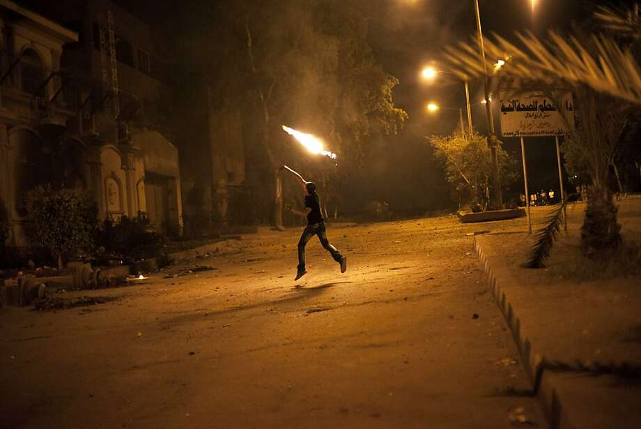 Unrest grows against Morsi:An Egyptian protester throws a Molotov cocktail at Muslim Brotherhood headquarters in the 