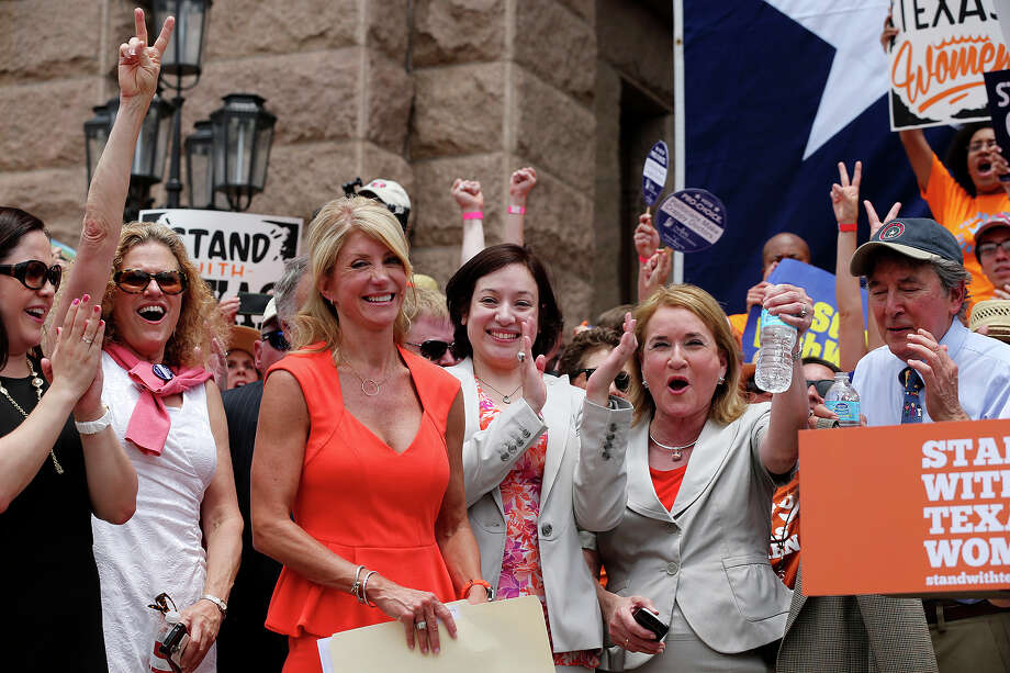 Senator Wendy Davis, third from left, smiles as she is introduced as the main speaker at the Stand With Texas Women Rally at State Capitol before the start of  the second special session, Monday, July 1, 2013. The anti-abortion legislation rally drew thousands of supporters. Photo: Jerry Lara, San Antonio Express-News / ©2013 San Antonio Express-News
