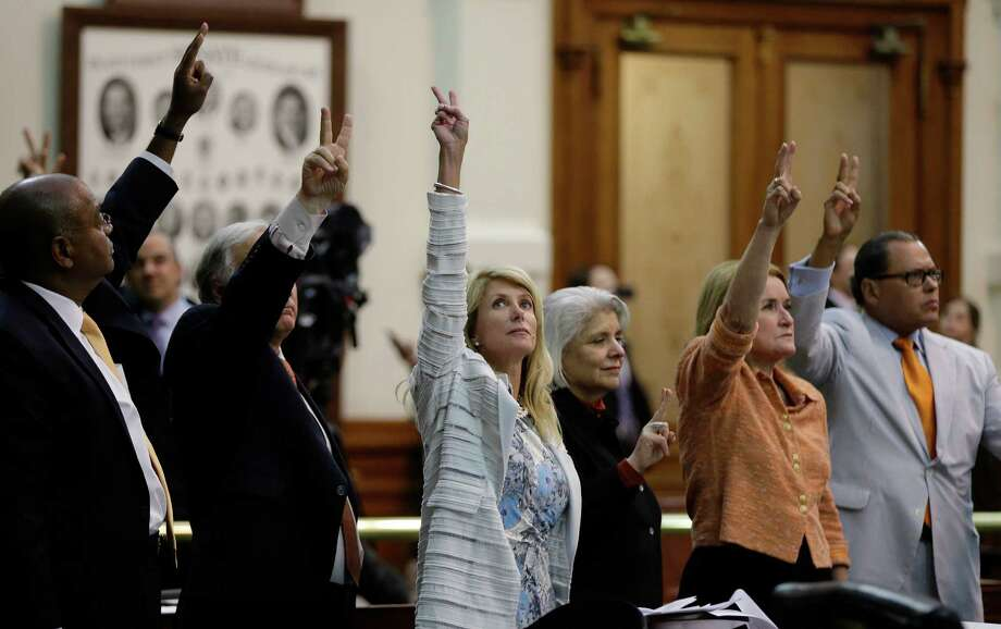 Sen. Wendy Davis, D-Fort Worth, center, along with other legislators, holds up two fingers to signal a no-vote as the session in which tried to filibuster an abortion bill draws to a close. A reader takes exception to an Express-News editorial that criticized the unruly behavior of pro-life supporters while letting the pro-choice advocates off the hook for displaying the same type of behavior. (AP Photo/Eric Gay) Photo: Eric Gay, Associated Press / AP