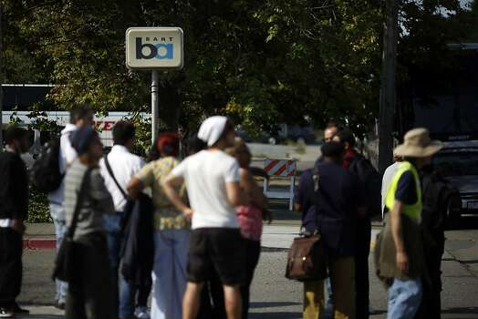People wait for BART commissioned buses to take them to San Francisco during strikes against BART outside of the West Oakland BART station in Oakland, Calif. on July 1, 2013. Photo: Ian C. Bates, The Chronicle