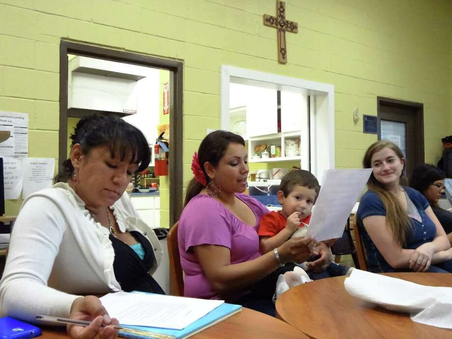 Veronica Colunga holds her son, Leonardo, while reading her original children's story at the Guadalupe Home as part of a Gemini Ink Writers in Communities workshop. Jessica Perez (left) and Elya Surface (right) listen and offer support. Photo: Photos By Steve Bennett / San Antonio Express-News