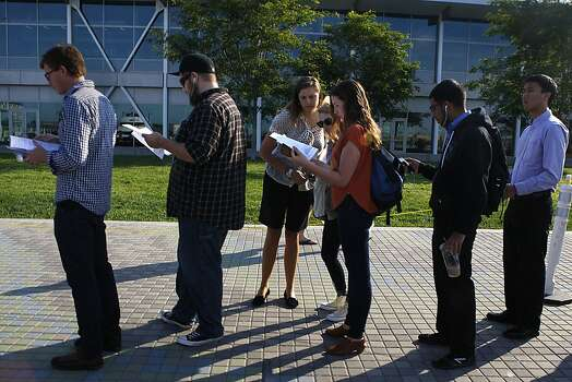 Commuters read the ferry schedule as they line up for the service at Jack London Square as City of Oakland and BART workers officially go on strike in Oakland, Calif.,  on Monday, July 1, 2013. Photo: Liz Hafalia, The Chronicle