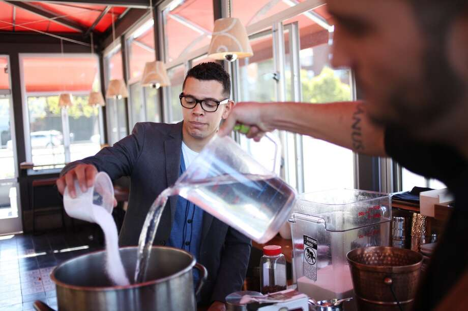 Joe Cleveland, left, adds sugar to a homemade anise tonic at Coqueta. He's making a Revolution GinTonic.