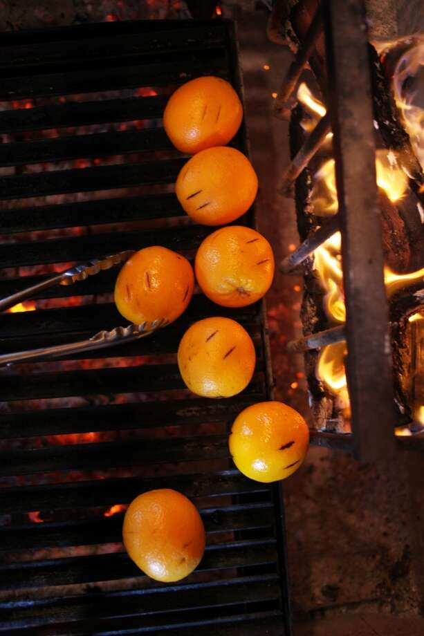 Barman Joe Cleveland grills oranges for a homemade anise tonic at Coqueta.