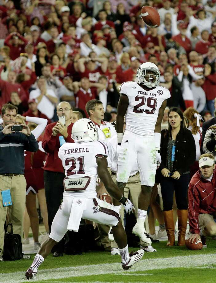 Texas A&M defensive back Deshazor Everett (29) reacts with teammate Texas A&M defensive back Steven Terrell (21) after intercepting a ball late in the fourth quarter, killing Alabama's chances to win in an NCAA college football game at Bryant-Denny Stadium in Tuscaloosa, Ala., Saturday, Nov. 10, 2012. Texas A&M beat Alabama 29-24. (AP Photo/Dave Martin) Photo: Dave Martin, Associated Press / AP