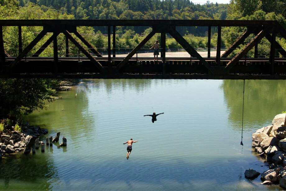 While we can't recommend this as a necessarily safe bet, entering a cool body of water from the height of a big rock or a low-hanging rain bridge (as shown here on the Stillaguamish River on Pioneer Highway near Stanwood) can be ultimately refreshing. Photo: DAVID BITTON, SEATTLE POST-INTELLIGENCER  / SEATTLEPI.COM