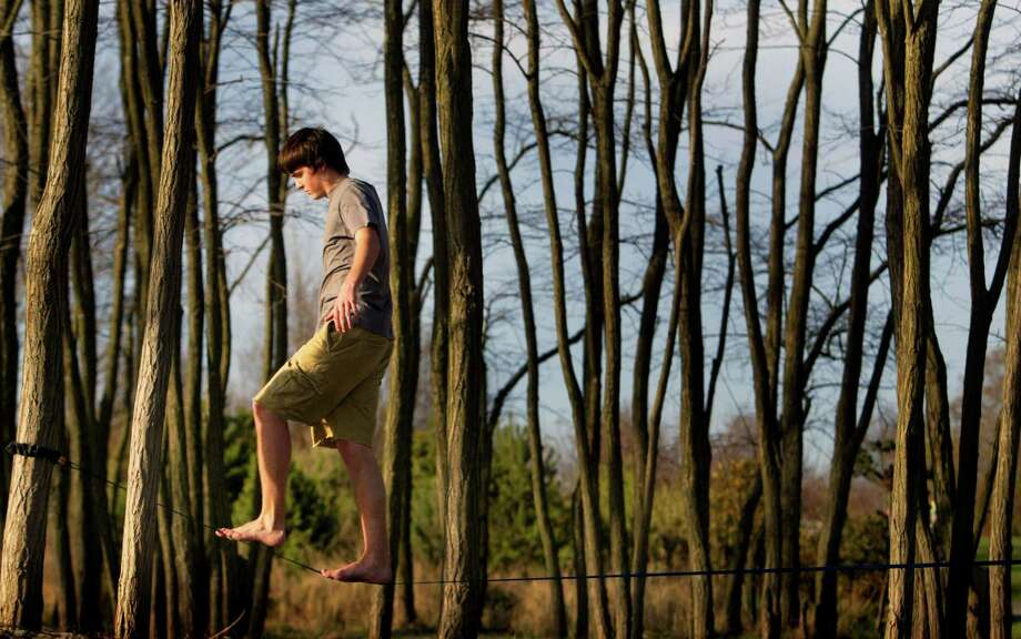 "Take up that new hobby you've been meaning to try. For instance, ""slacklining"" which uses webbing and differs from tightrope walking in that the line is not pulled taught, allowing for bounce and movement in the line. It is like walking on a giant rubber band. Photo: Joshua Trujillo, Seattle Post-Intelligencer / SEATTLEPI.COM"